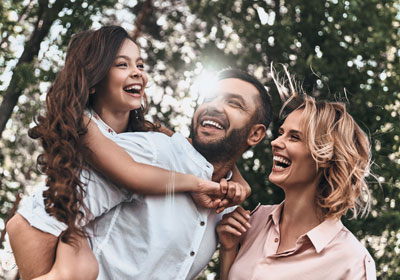 goodencenter-mental-health-treatment-photo-of-Happy-young-family-of-three-smiling-while-spending-free-time-outdoors