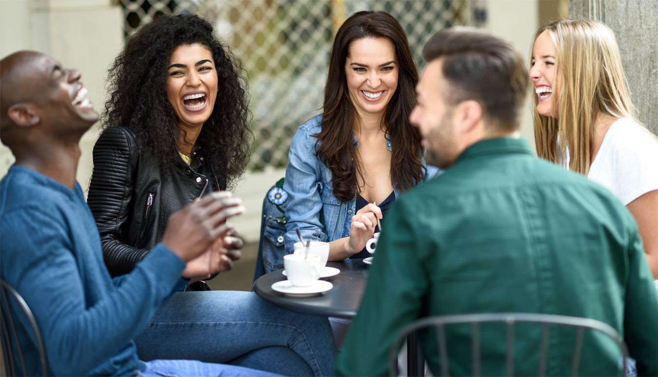 goodencenter-photo-of--Three-women-and-two-men-at-cafe,-talking,-laughing-and-enjoying-their-time