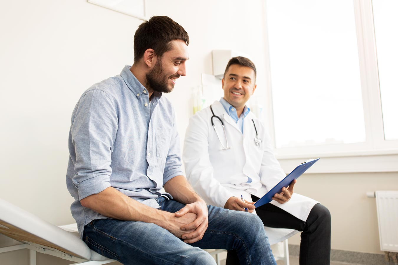 gooden-center-prescription-drug-addiction-photo-of-smiling-doctor-with-clipboard-and-young-man-patient-meeting-at-hospital