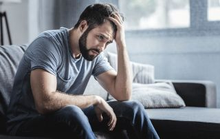 goodencenter-10-symptoms-of-depression-photo-of-a--Sad-unhappy-handsome-man-sitting-on-the-sofa