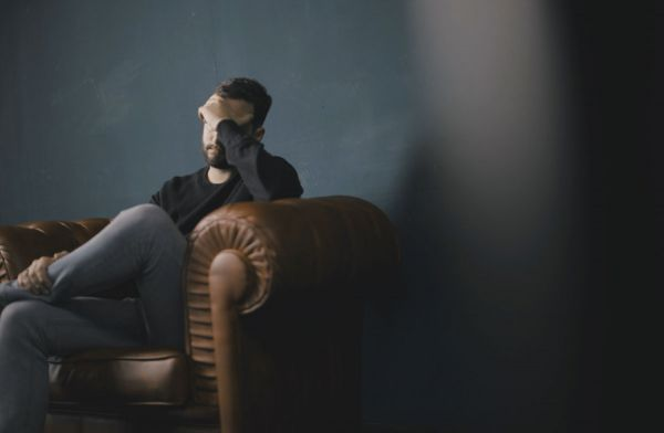 goodencenter-10-symptoms-of-depression-photo-of-a-man-sitting-on-sofa-against-wall