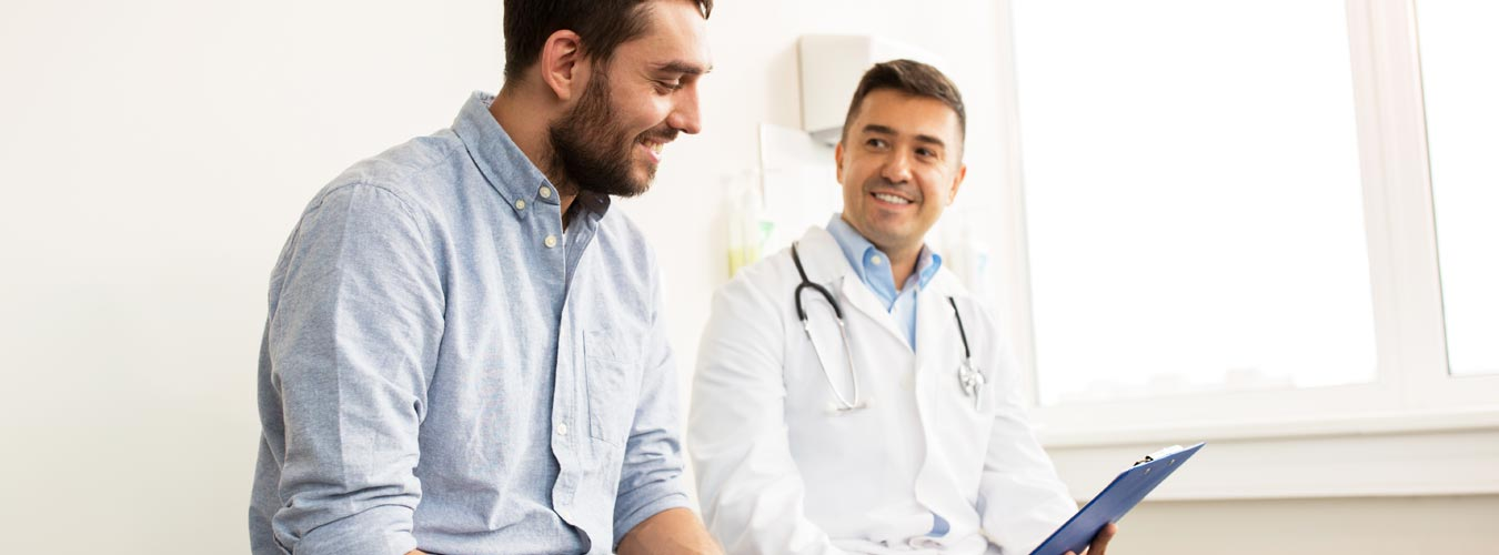 goodencenter-questions-medical-professionals-photo-of-smiling-doctor-with-clipboard-and-young-man-patient-meeting-at-hospital