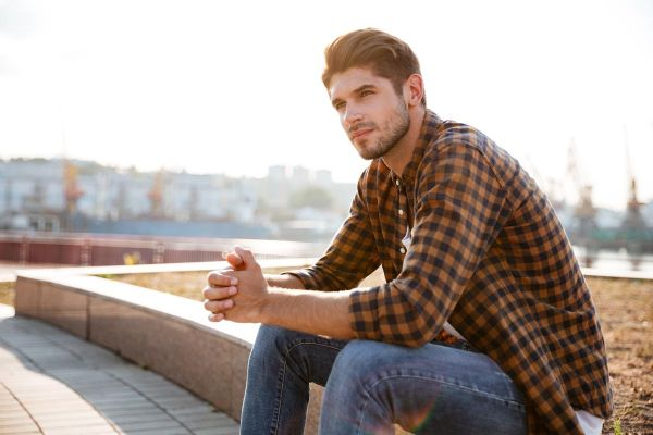 goodencenter-Sleep-and-Mental-Health-photo-of-a-Pensive-young-man-in-plaid-shirt-sitting-and-thinking-outdoors