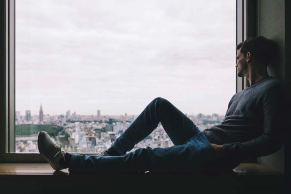 goodencenter-The-LGBTQ+-Community-and-Substance-Use--photo-of-a-lonely-man-sitting-near-the-window