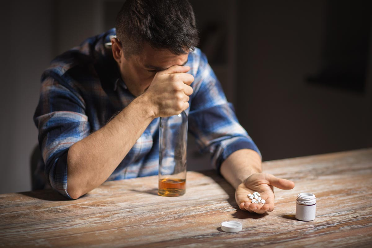 goodencenter-Why-Alcohol-and-Antidepressants-Should-Not-be-Mixed-photo-of-unhappy-drunk-man-with-bottle-of-alcohol-and-pills