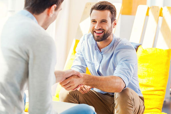 goodencenter-women's-Mental-Health-Treatment-photo-of-Closeup-of-men-during-pysch-therapy photo-of two happy-young-men-shaking-hands