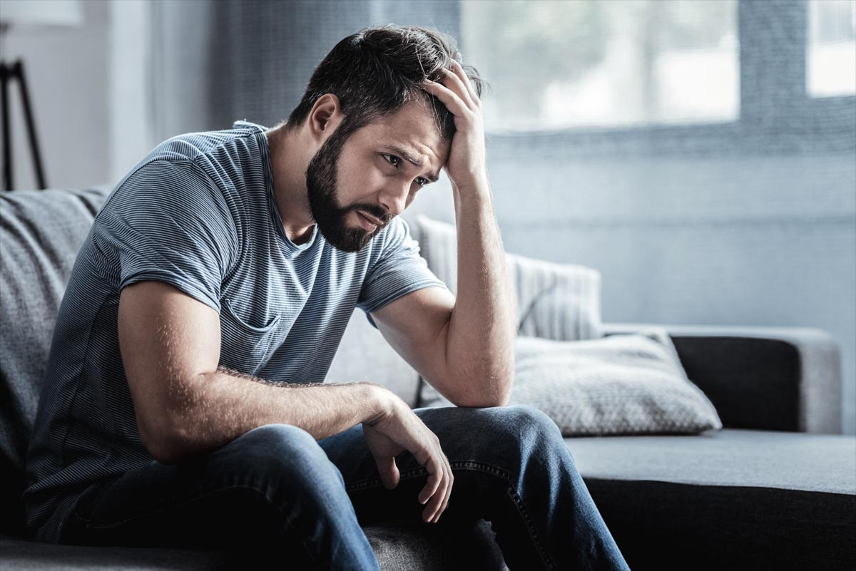 goodencenter-mens-issues-in-substance-abuse-treatment-photo-of-sad-unhappy-handsome-man-sitting-on-the-sofa