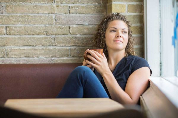 goodencenter-Mindfulness-for-OCD-Tips-and-Skills-for-Living-photo-of-a-thoughtful-woman-holding-coffee-mug