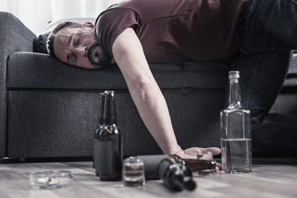 goodencenter alcohols effect on the body photo of a Drunk bearded adult man lying on the sofa