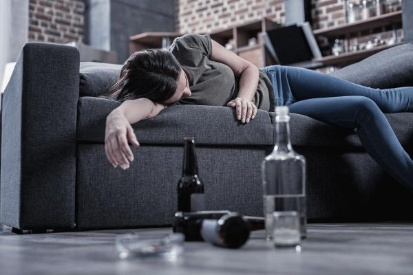 goodencenter alcohols effect on the body photo of a Sleepy drunk young woman lying on the sofa