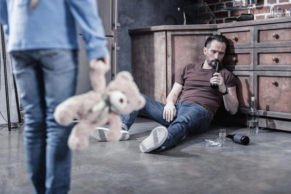 goodencenter alcohols effect on the body photo of a drunk man sitting on the kitchen floor and drinking while not caring about his daughter