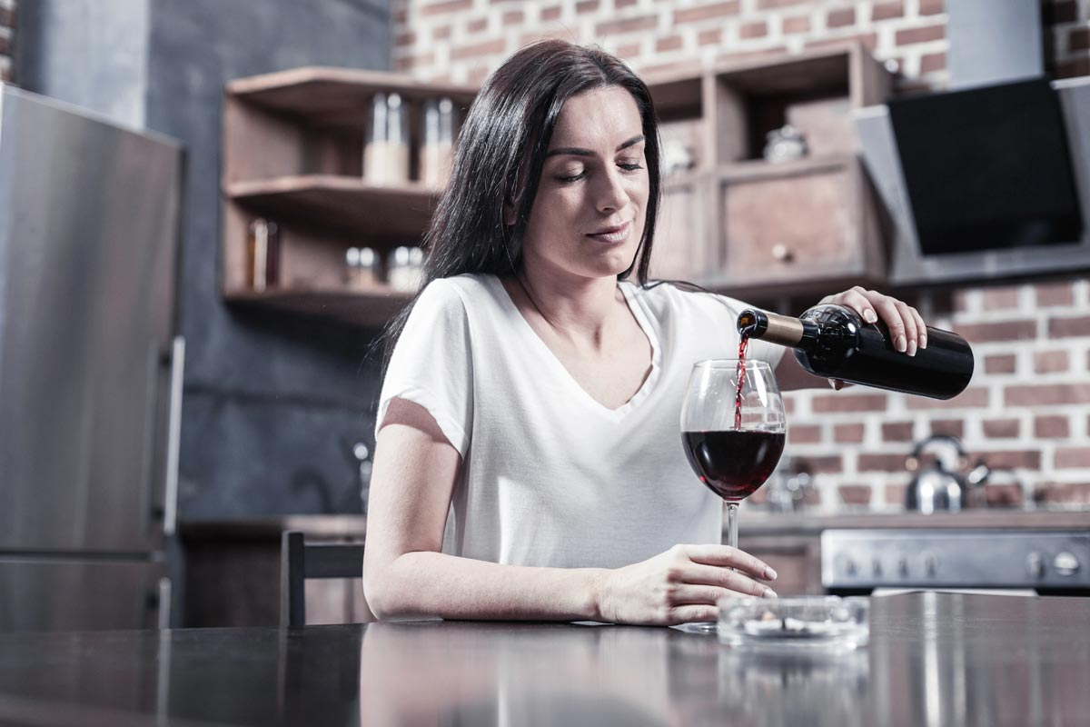 goodencenter alcohols effect on the body photo of a woman holding a bottle while pouring wine