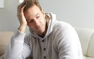goodencenter 5 Signs of Depression Relapse and How to Avoid Them photo of a depressed man sitting on a couch