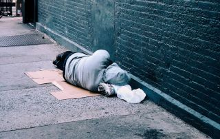 gooden center The Connection Between Homelessness and Addiction photo of a homeless man lying in the street