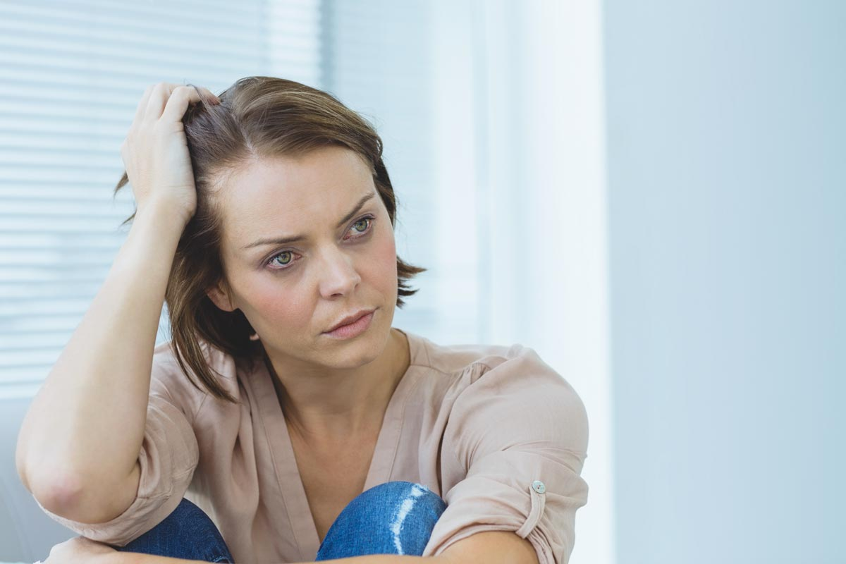 goodencenter How to Identify Signs of Mental Illness in a Loved One photo of a depressed woman looking away at home