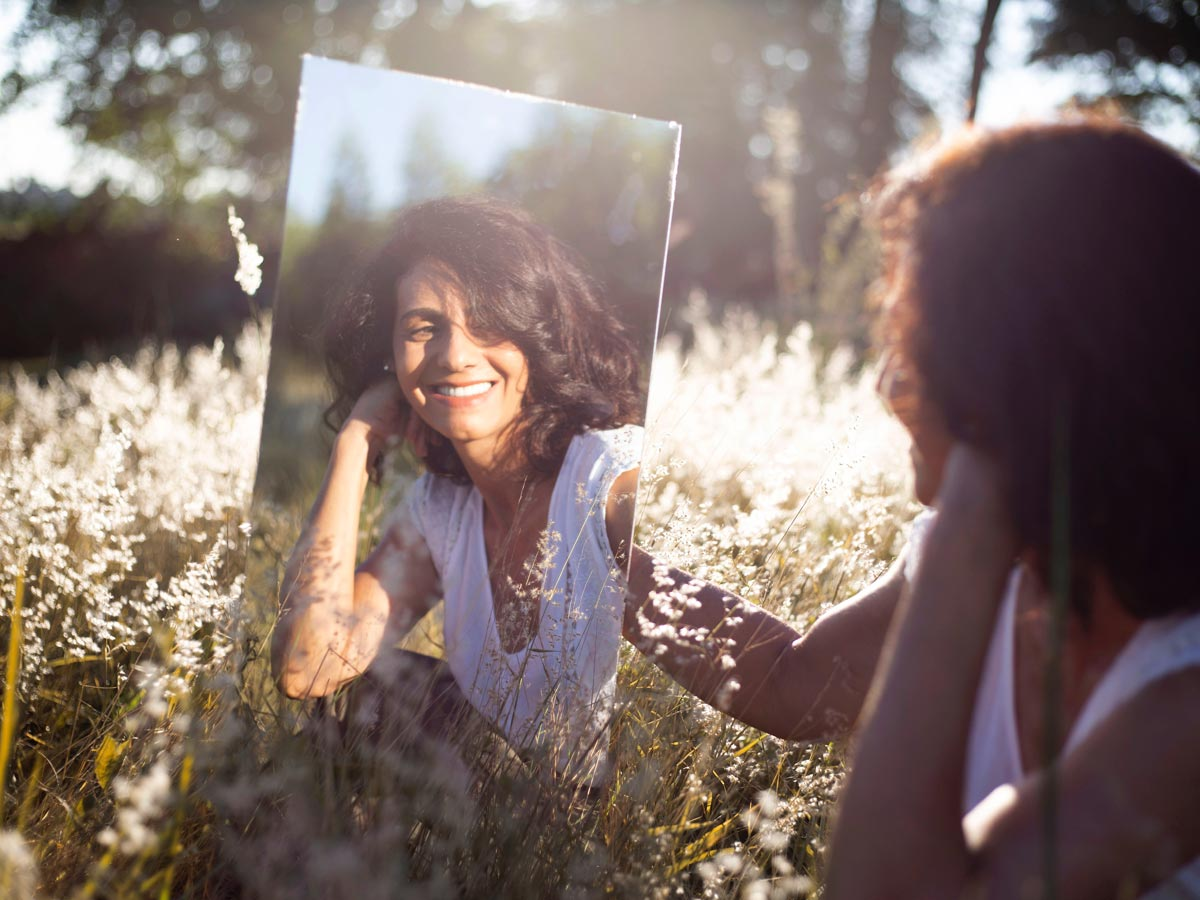 a photo of a woman with mental health disorder sitting on the grass looking at the mirror, narcissism