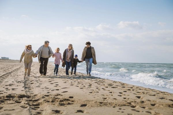 Photo of big multigenerational family walking together on beach at seaside after attending a family therapy