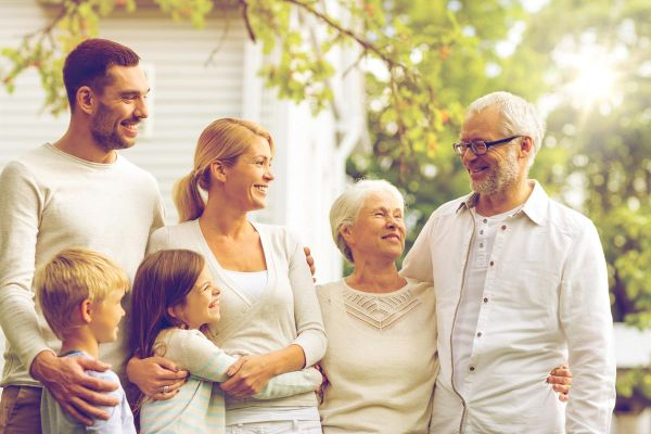 photo of a happy family standing in front of a rehab facility during for family therapy